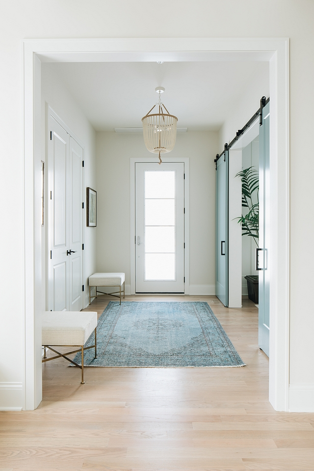 The entryway couldn't possibly be more welcoming, with so much natural light streaming in even when the door is closed. The ottomans provide anchoring to the long wall without being bulky or taking up too much space. Light Fixture can be found  here .