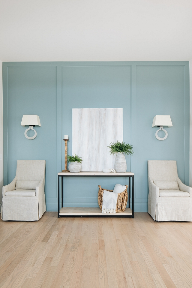 This art nook is especially powerful with the neutral piece displayed proudly against the aqua paneled wall.