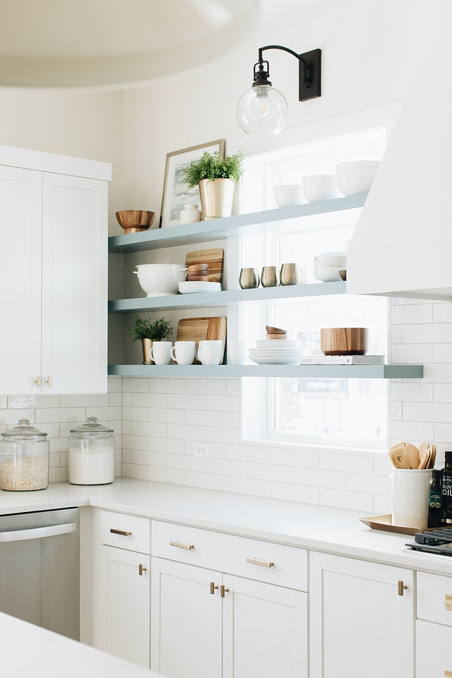 """I knew I wanted the element of floating shelves in this kitchen but couldn't really find a good spot. The horizontal lines on the windows inspired me to take the shelves all the way across the windows on the main wall of the kitchen. When we solidified the beach theme the color I choose for the island and shelves was the next decision. The color is actually far darker and more grey in person than in the photos. I based the color of the island on the tile I chose for the fireplace."" – Julie Howard."