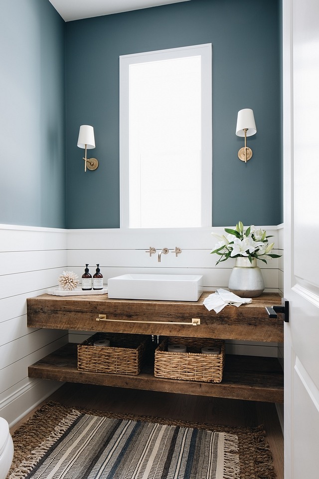 The blue on the powder room walls is the darkest hue seen in the home. I love seeing designers take risks in powder rooms — they're meant to be bold since they're tucked away and don't have to match the rest of the home.