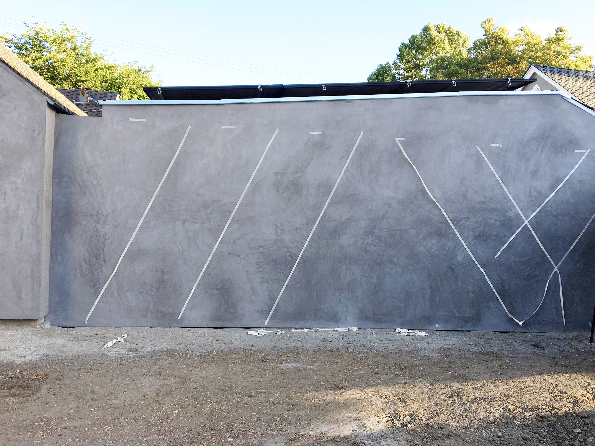 Here's what its looking like now. We covered both walls with stucco so it feels cleaner and more consistent.   Next, we are going to espalier vines up the wall in a criss-cross fashion.  Here's my lame tape job looking at different angles.