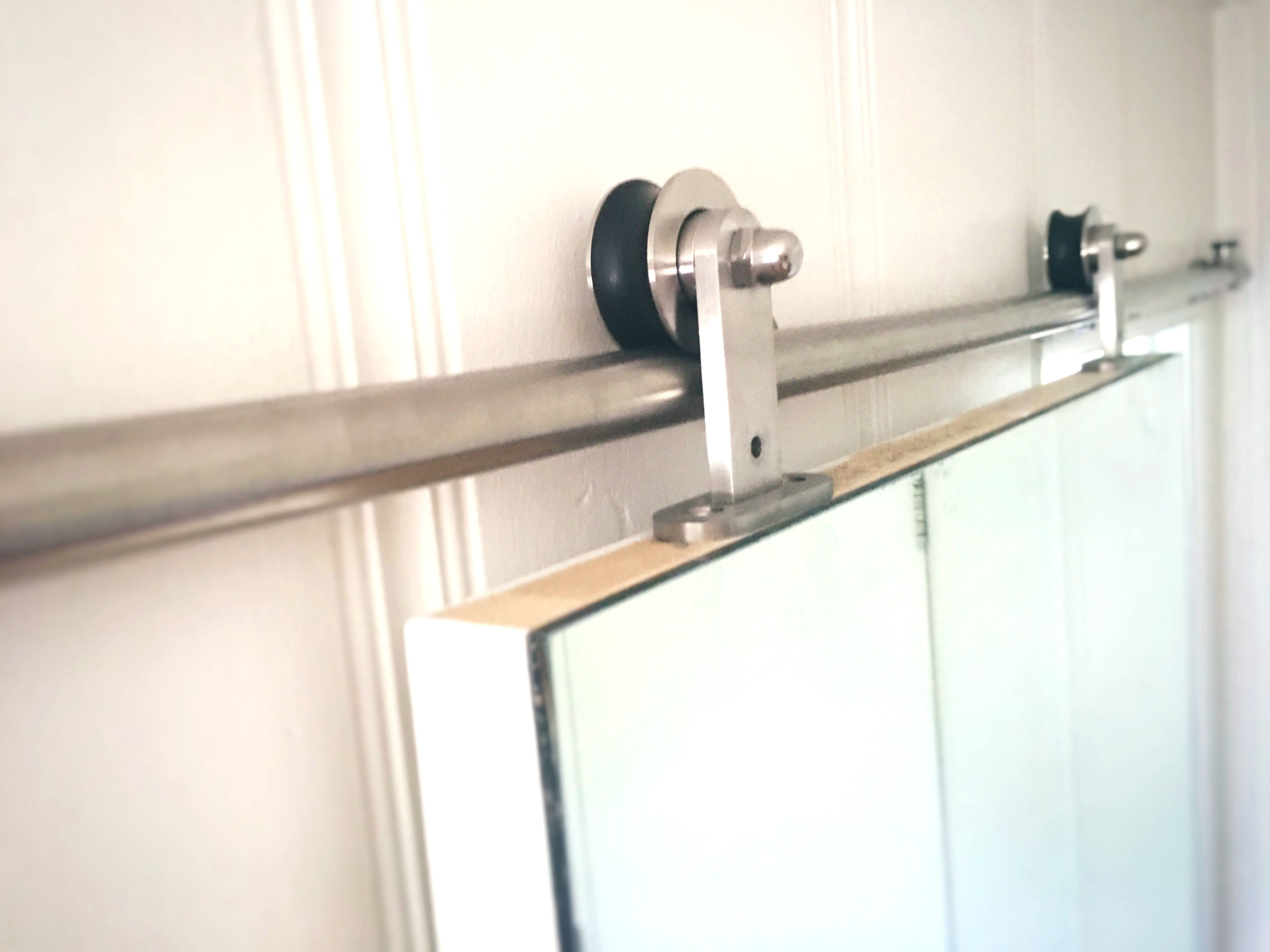 Barn door hardware is getting very popular. You can find it everywhere online.  Here  is a relatively inexpensive one.