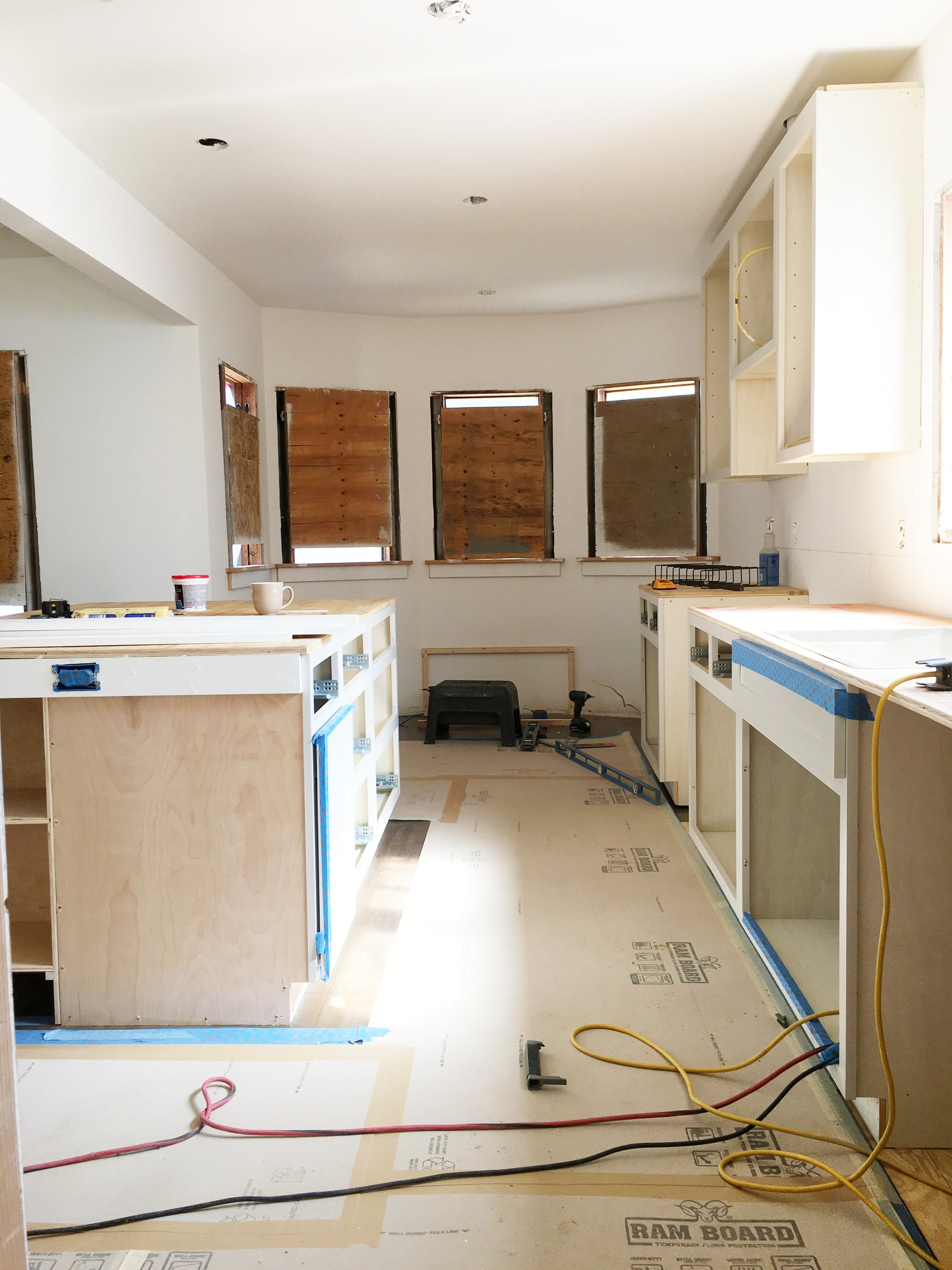 Hardwood floors have been covered to protect the new refinishing.Cabinets have been installed.