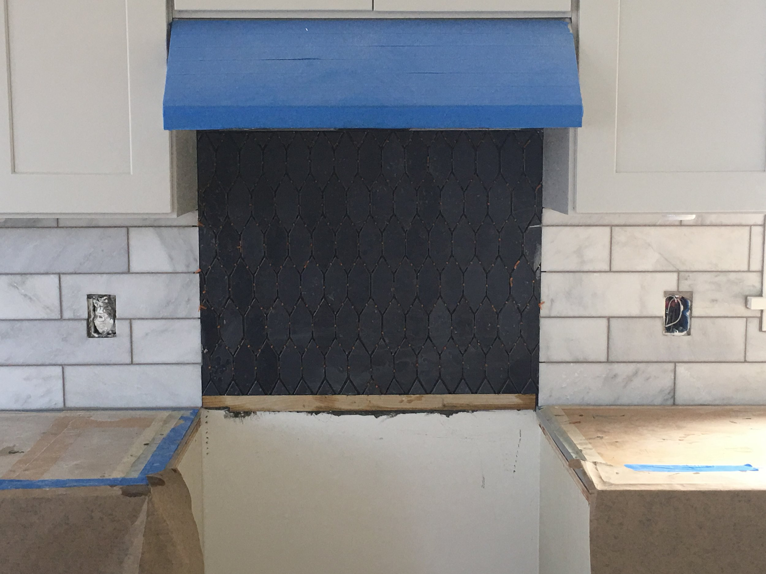 Above you'll see the two tiles laid out and ready to be installed. And, here is the backsplash laid in. The marble tile has been grouted with Oyster Gray grout. We'll grout the Heath tile tomorrow with the same grout. It just needs to set overnight.