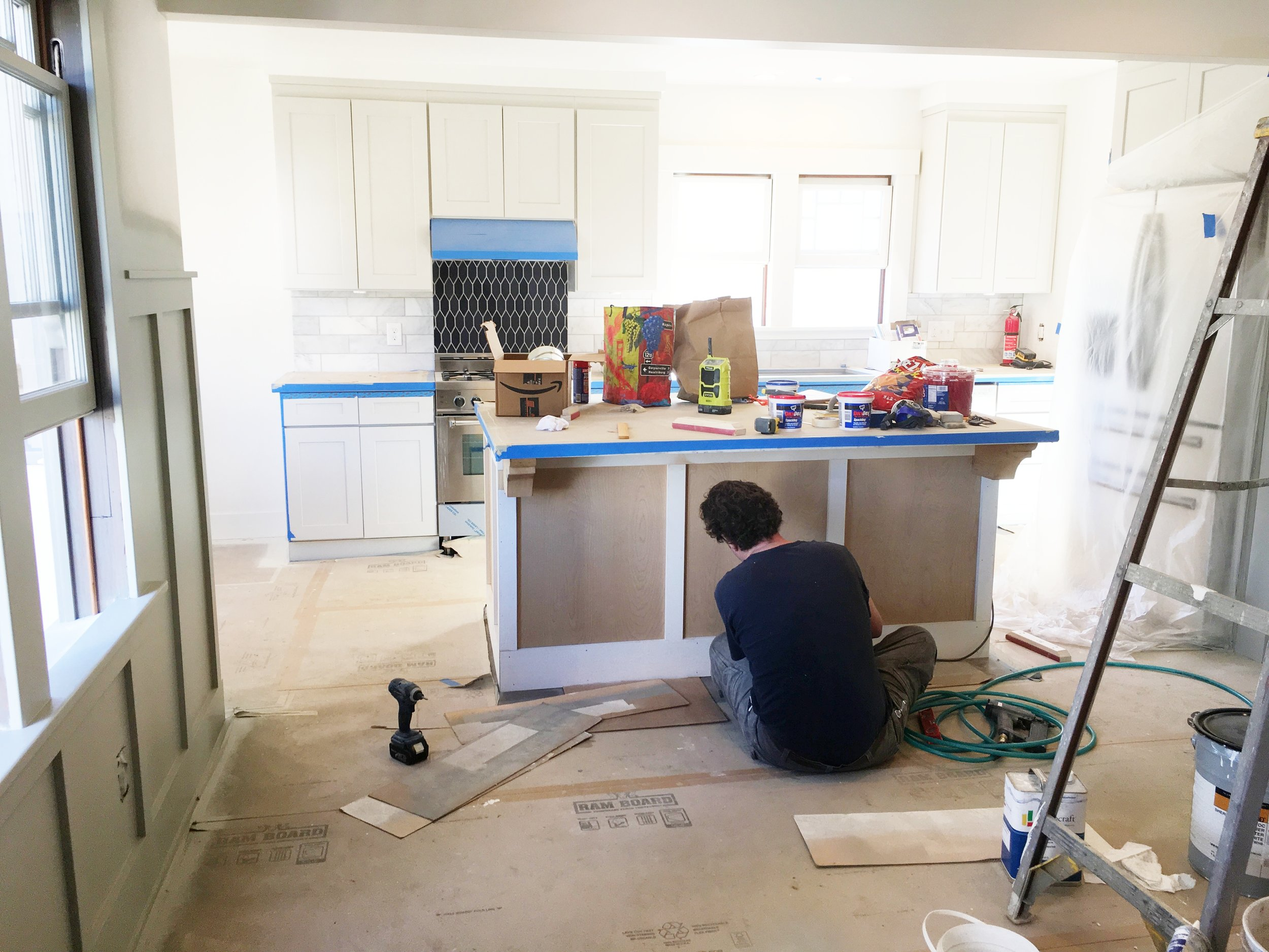 Lance installing wainscoting on the kitchen island.