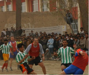 A fan watches from a tree as Coalition players (red) take on Afghans (green and white). (Photo courtesy: Emily Anders)