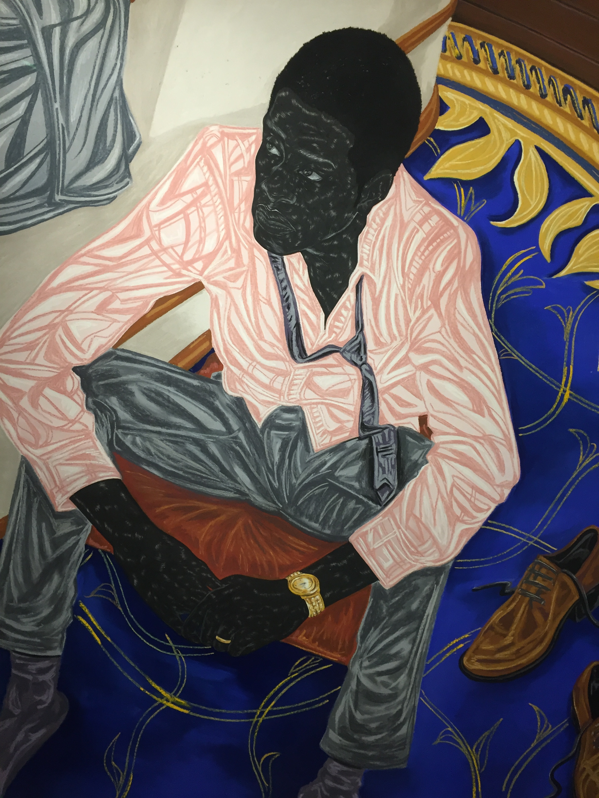 Black male, well groomed, gorgeous shade of blue, gold watch, patterned carpet, shoes off, wedding ring, loose tie, pink shirt, jacket thrown over adjacent chair, seated upon the edge of an opulent chair, fabric that glistens, fabric that hangs with grace, sheepish look.