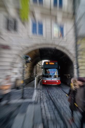 Un tramvaitrece razant pe lângă pietoni
