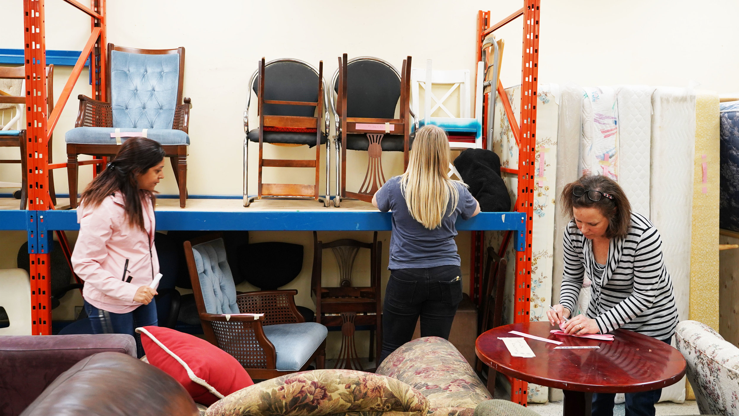 Vicki Dignard and Fran Laurendeau guiding a family through the Matthew House Ottawa Furniture Bank showroom.