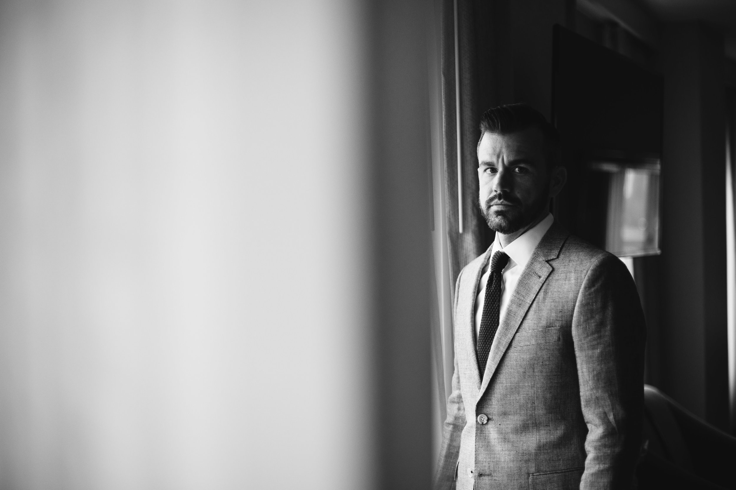 A black and white portrait of the groom before the wedding at this Battello Wedding in Jersey City, NJ