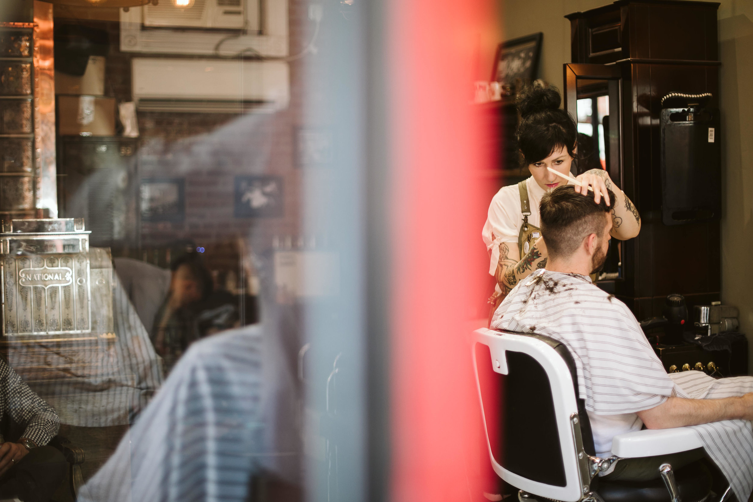The groom getting a pre-wedding haircut at the barber shop at this Battello Wedding in Jersey City, NJ