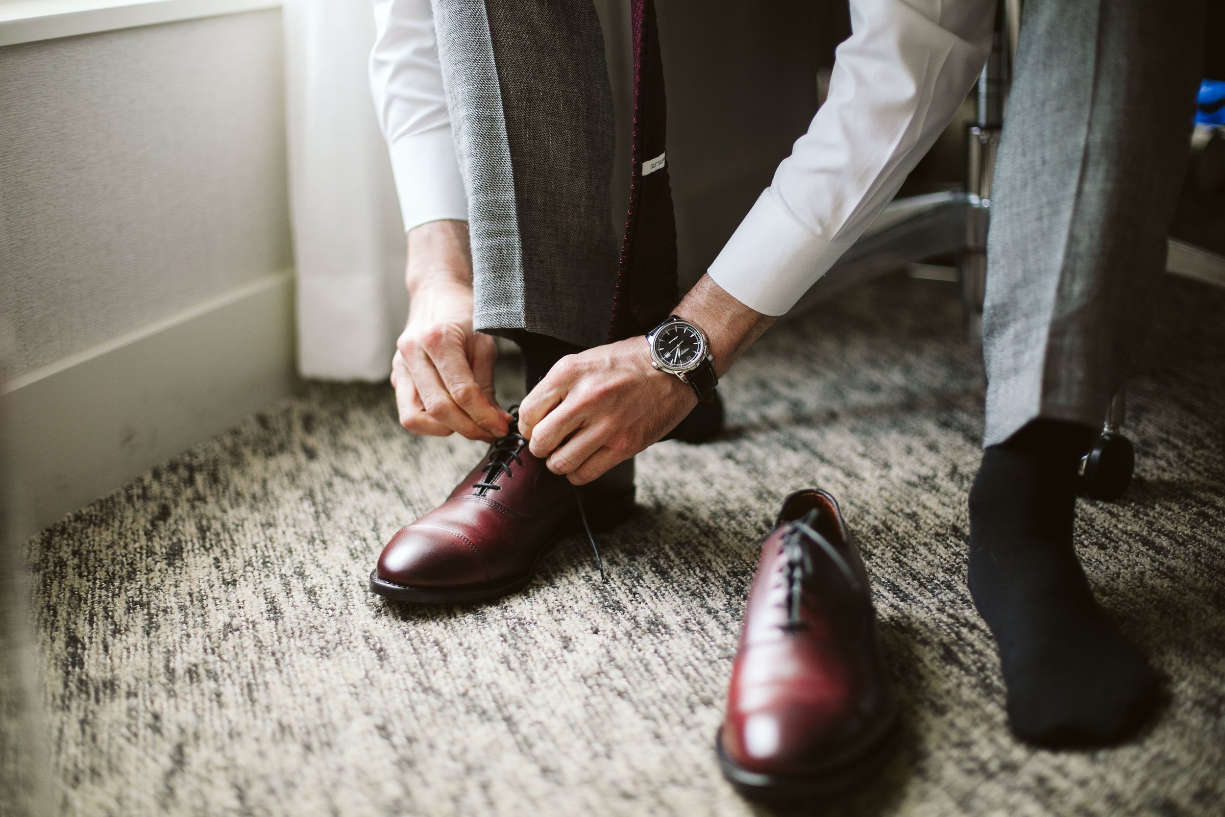 The groom getting ready and putting on his shoes at this Battello Wedding in Jersey City, NJ