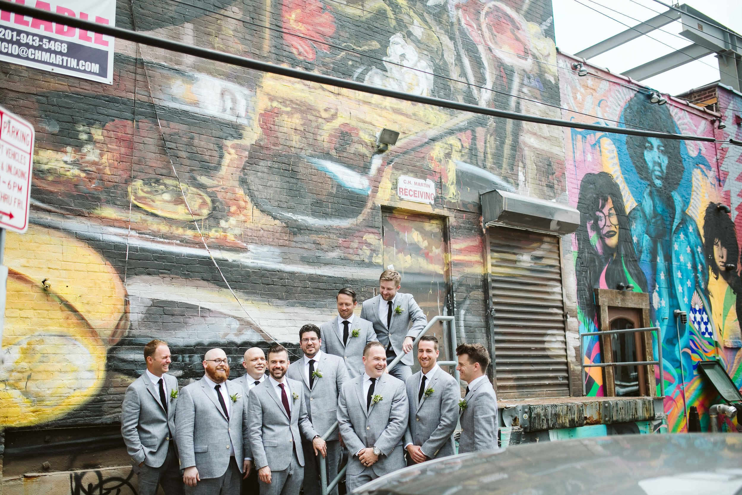 The groom and groomsman walking to the wedding in their gray suits by a graffiti wall at this Battello Wedding in Jersey City, NJ