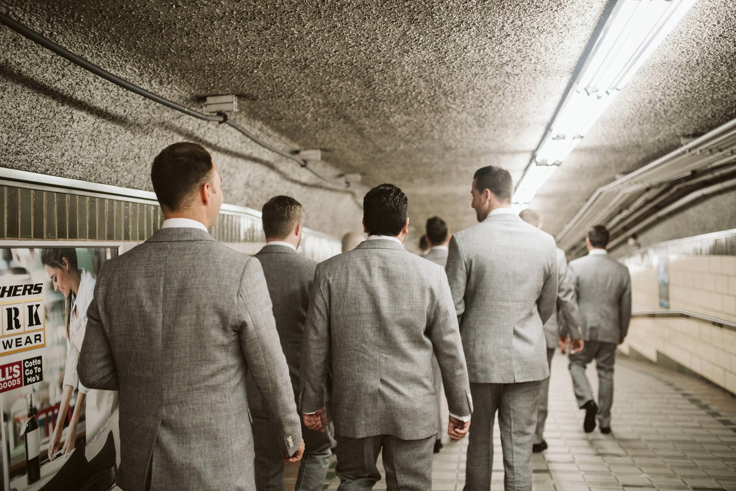 The groom and groomsman walking to the wedding in their gray suits in the Subway at this Battello Wedding in Jersey City, NJ