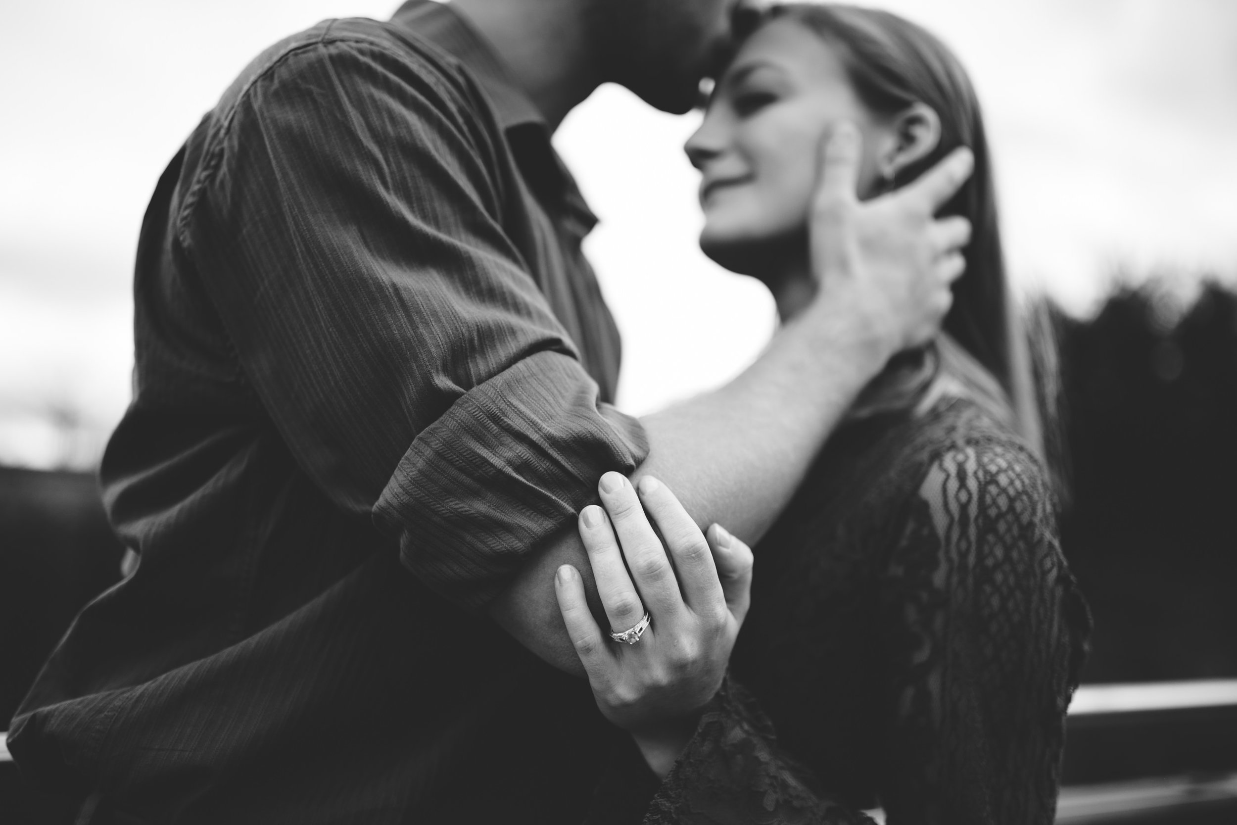 black and white engagement photo with forehead kiss