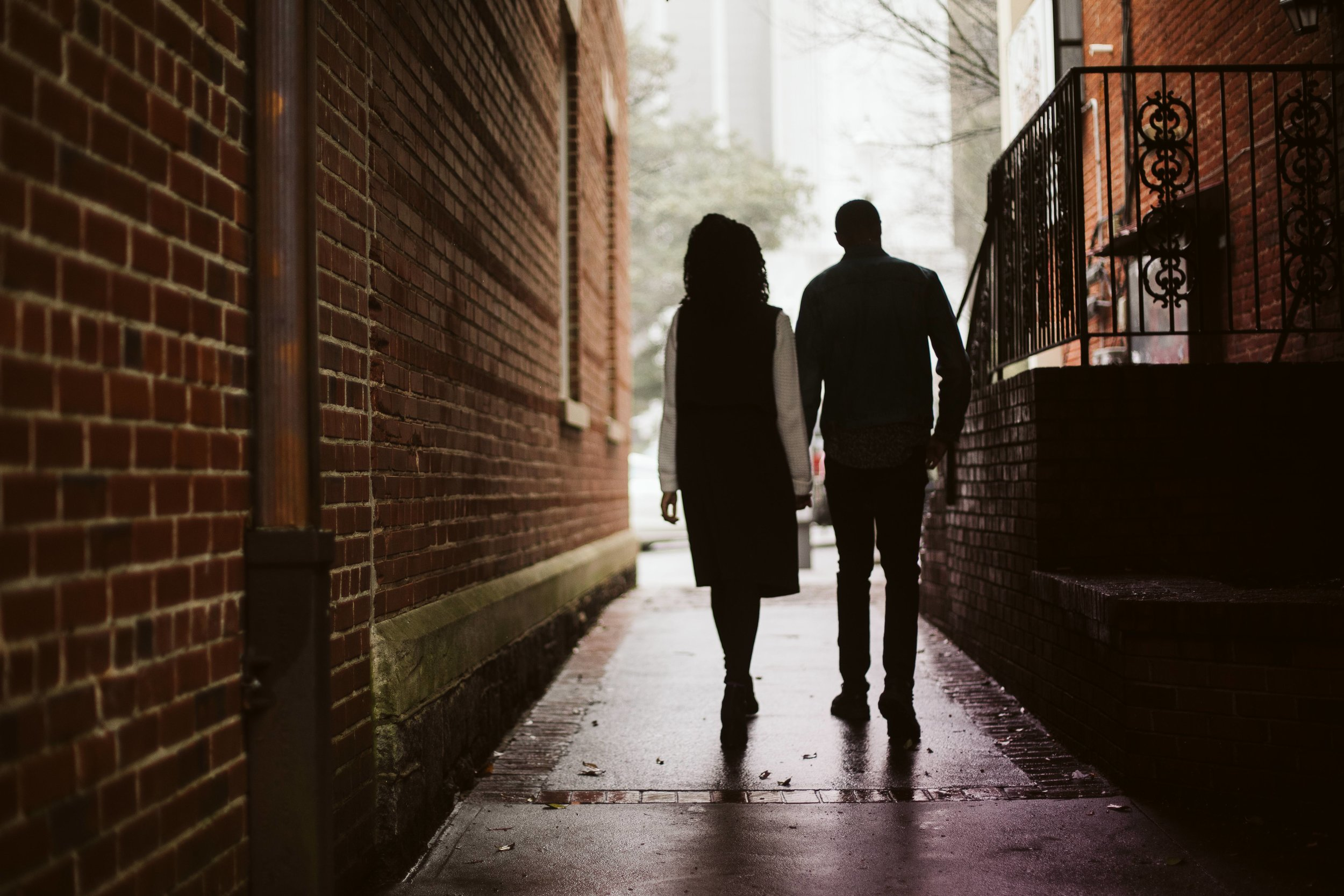 couple silhouettes by a brick wall for engagement photo