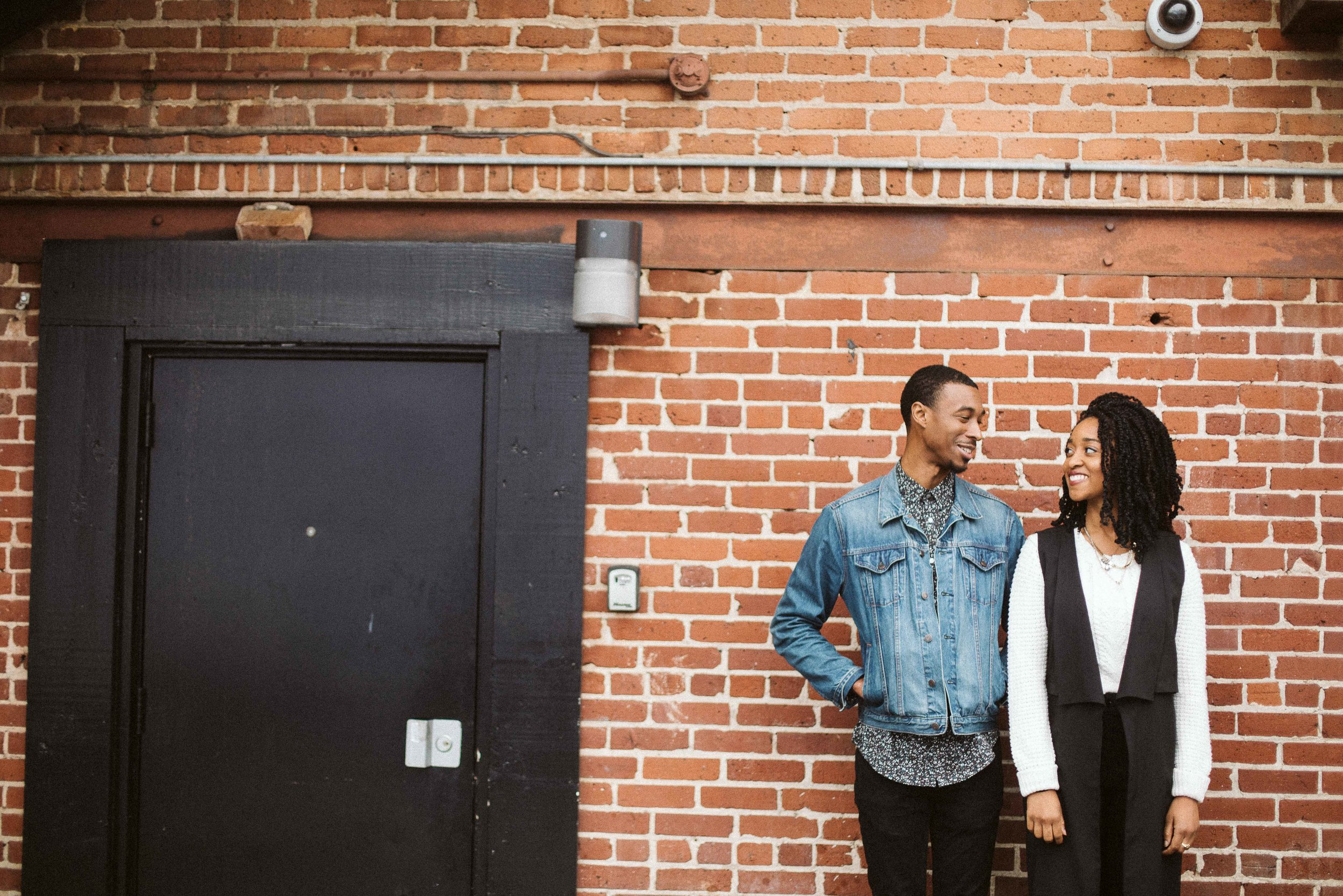 brick wall and black door behind the couple for engagement photo