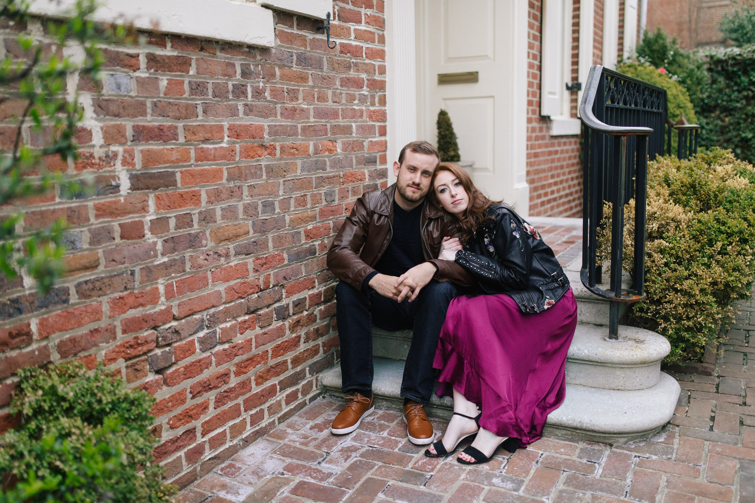 A leather jacket and maroon dress and a brick wall at this DC Area Engagement Shoot - Alexandria, VA