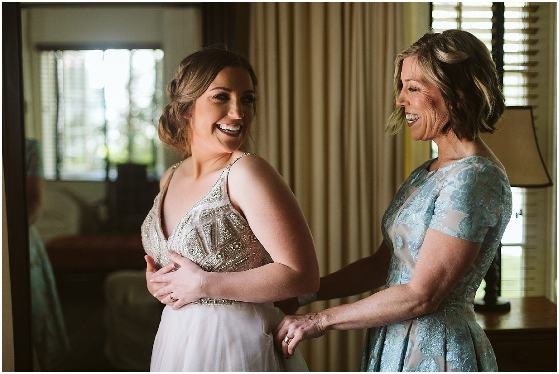 bride's mom zips up wedding gown