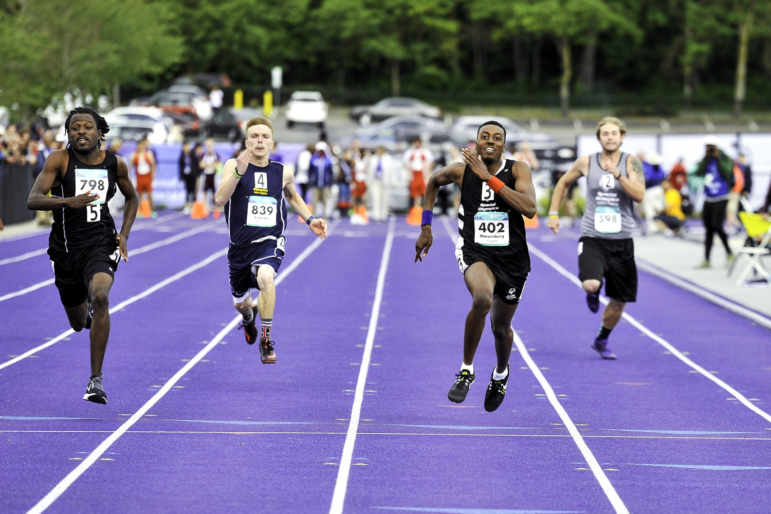 Athletes approaching the finish line at the 100 meter dash on the Husky Track of the University of Washington.