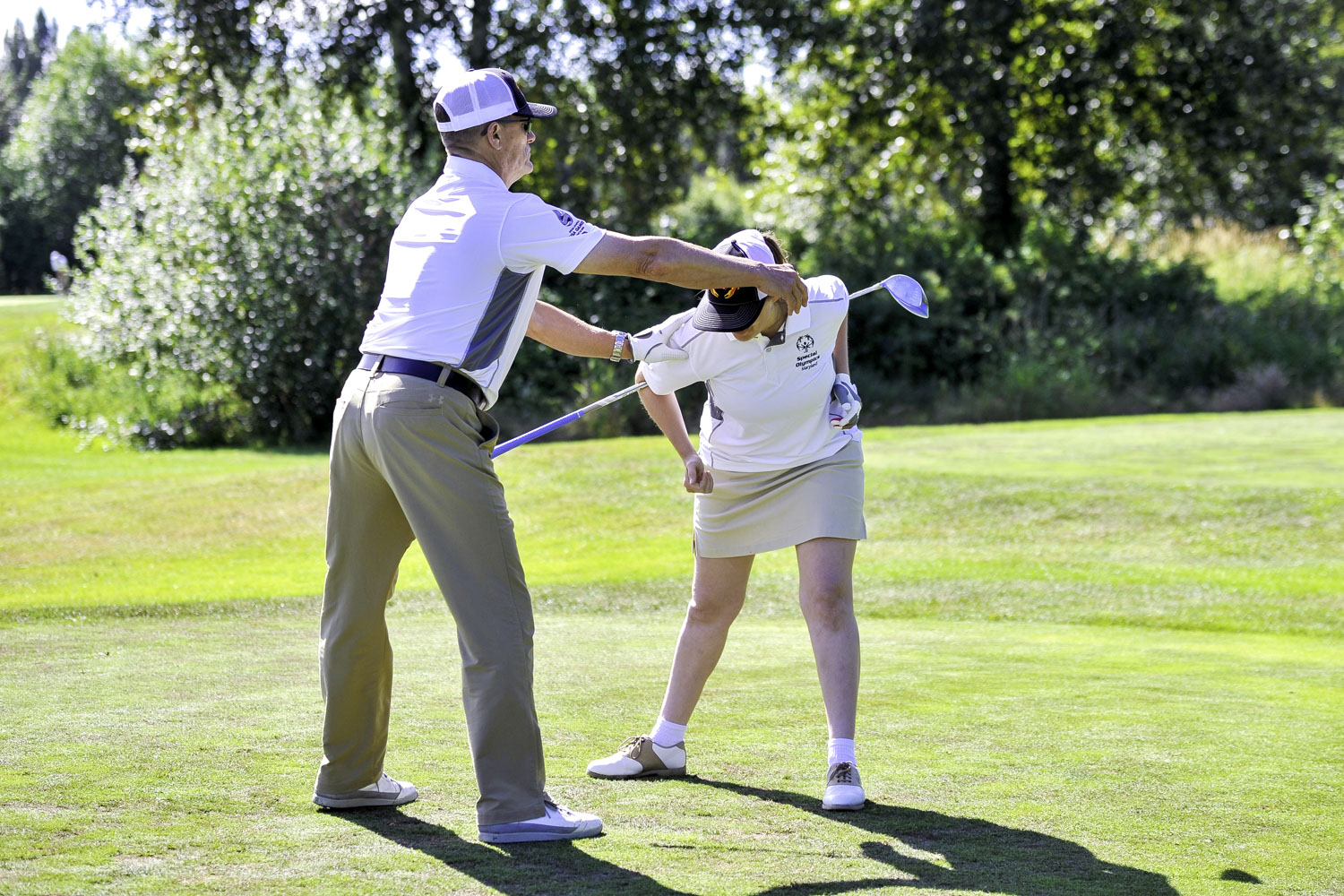 Golf coach helps his athlete stretch and relax at the tee box before her first shot at the Willows Run Golf Club in Redmond, Washington.