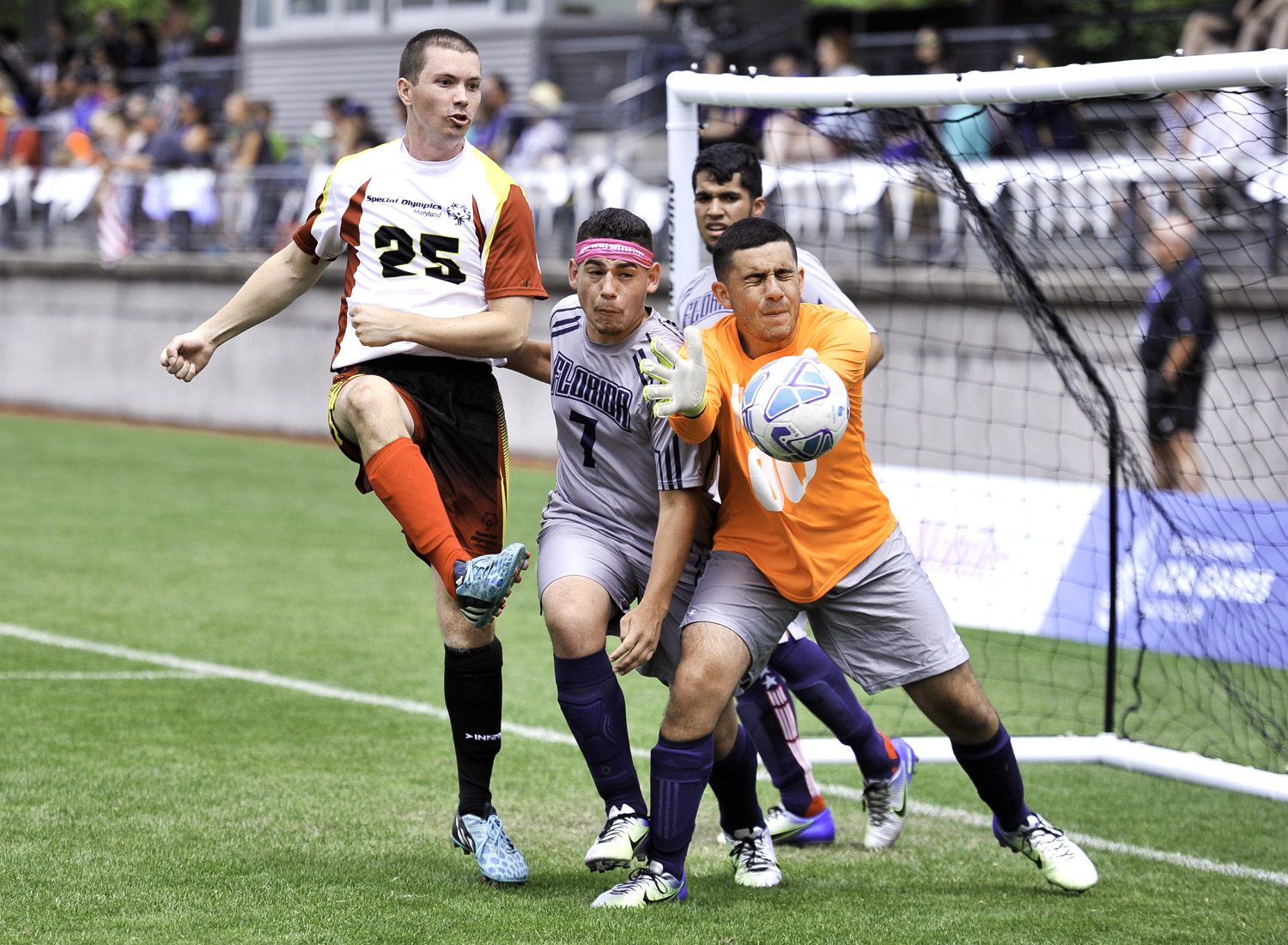 Team Maryland player attempts to score and Team Florida goalkeeper deflects the ball on the Championship Field of the University of Seattle.