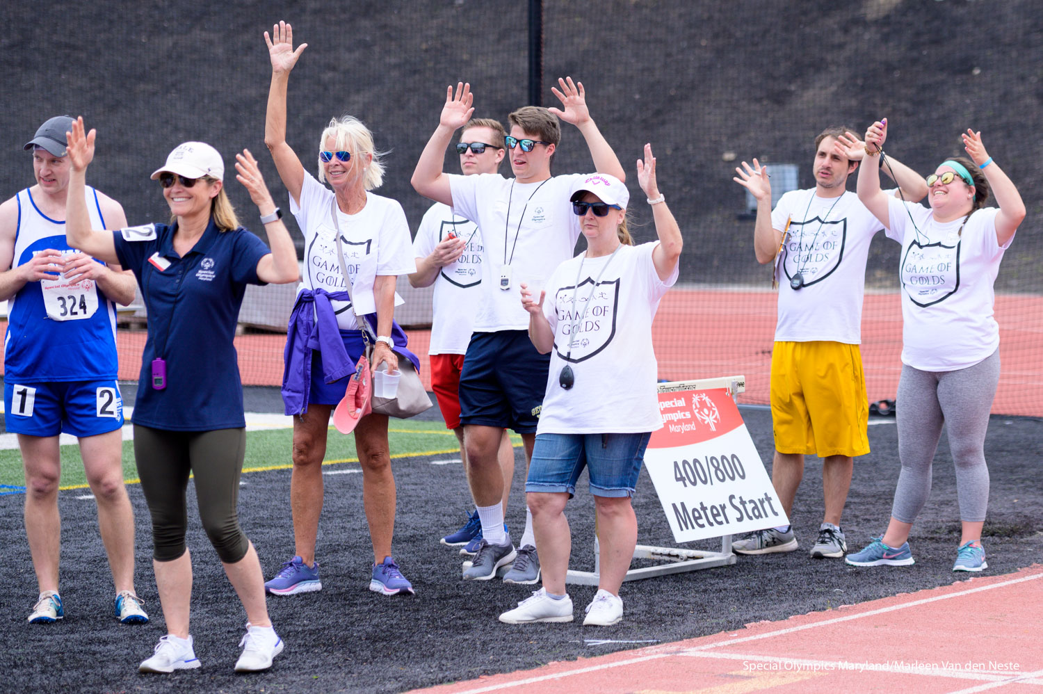 Judges and volunteers applauding a deaf runner at the finish line on the track of Unitas Stadium, Towson University, MD. on Sunday, June 9, 2019.