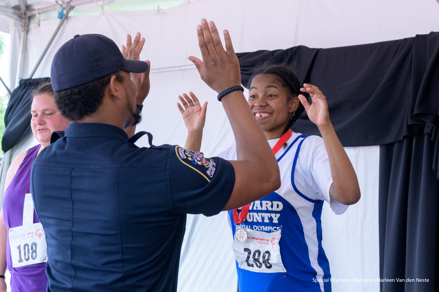 Athlete high-fiving a law enforcement officer after receiving a silver medal from him in the Awards tent at Unitas Stadium, Towson University, MD. on Sunday, June 9, 2019.