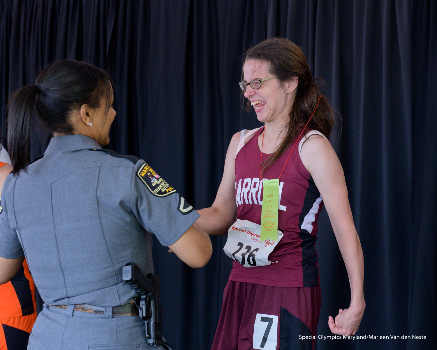 "Excited athlete shaking hands with a law enforcement officer upon receiving a 6th place ribbon reading ""skill, courage, sharing, joy"" in the Awards tent at Unitas Stadium, Towson University, MD. on Sunday, June 9, 2019."