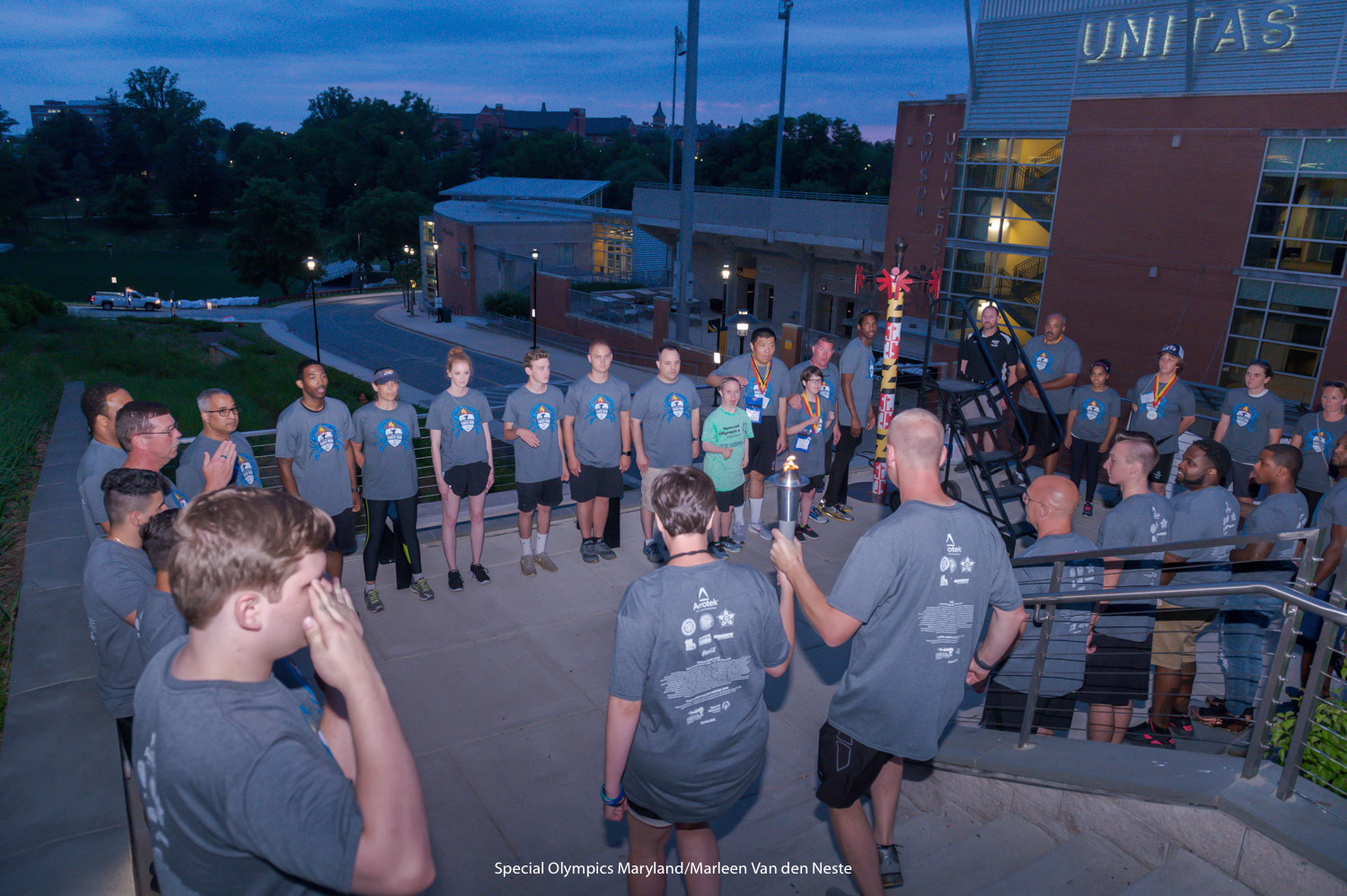 Two athletes carry the Olympic torch to its final destination in front of Unitas Stadium at Towson University, MD at the end of the Opening Ceremony. They are surrounded by Law Enforcement Torch Runners and athletes. The torch will remain lit until the Summer Games are completed.