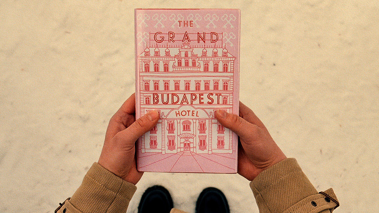 """A scene from Wes Anderson's   """"The Grand Budapest Hotel.""""   The lovely design of the book cover in this scene was an inspiration for the travel information card. Photo courtesy of  Fox Searchlight."""