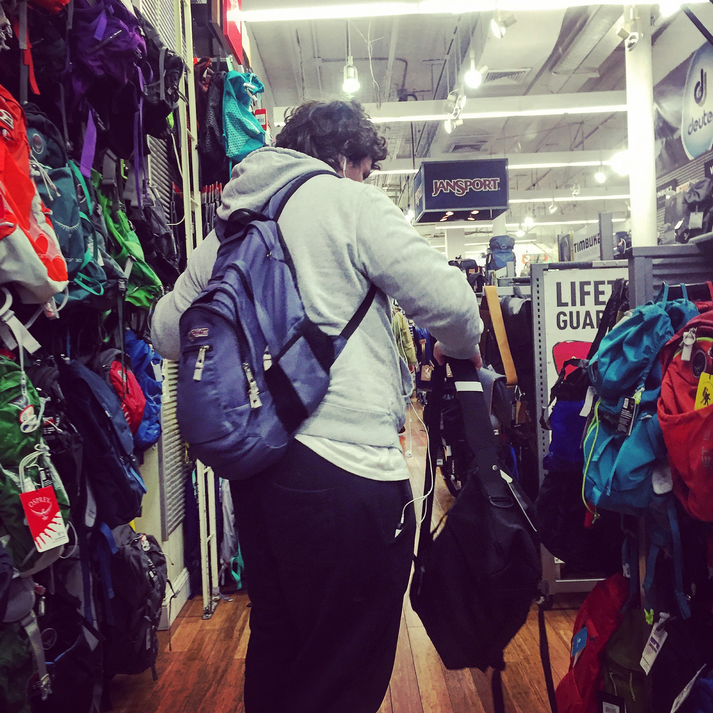 A customer tries on a backpack.