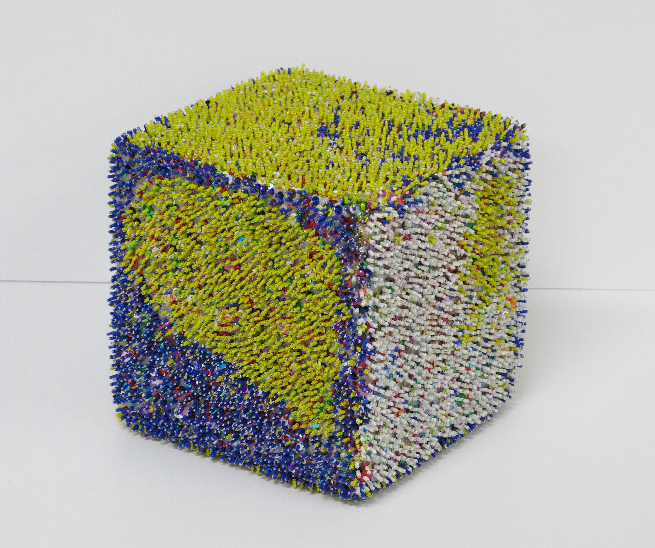 [IMAGE - 12 INCH CUBE COVERED IN COLORFUL SEQUENCE TEXTURE. MONICA VALENTINE, COURTESY CREATIVE GROWTH ARTS CENTER, 2015]
