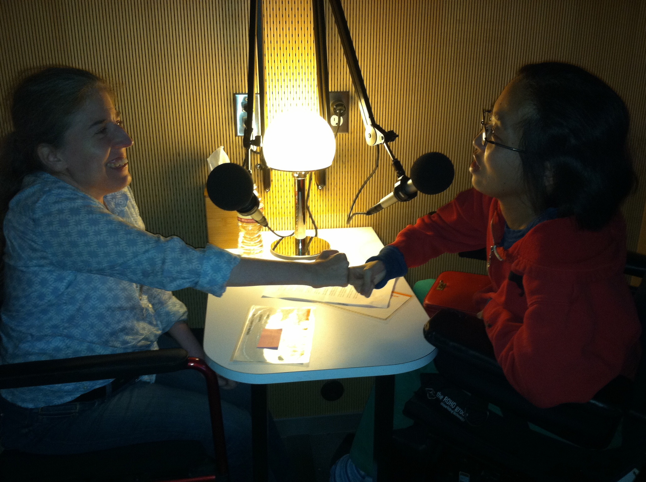 IMAGE - Fist-bumping during an interview at StoryCorps San Francisco with Ingrid Tischer (left), Director of Development, DREDF and Alice Wong (right), Head Honcho, Disability Visibility Project, 2014. Image courtesey Alice Wong, DVP.