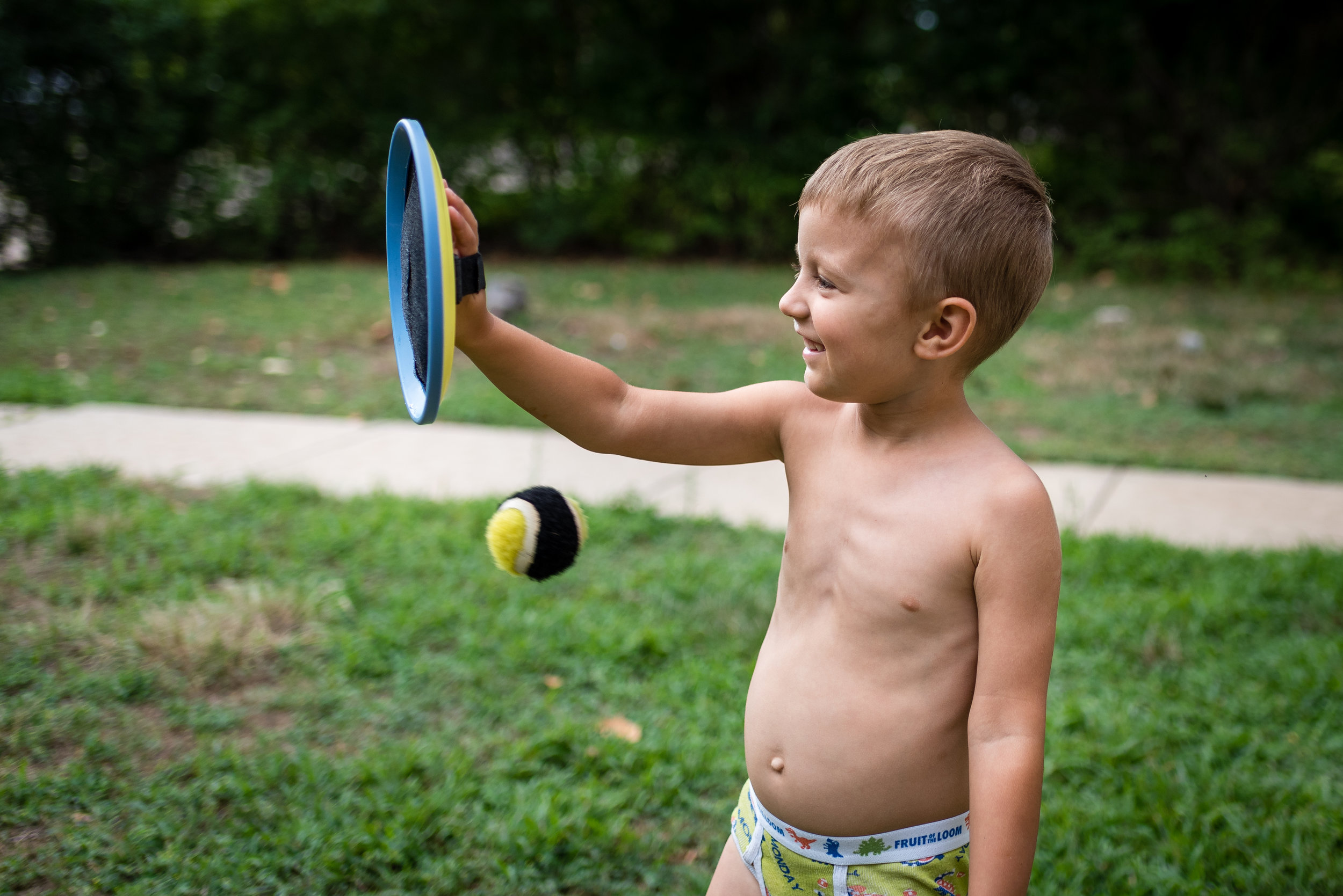 "We had a family gathering in Manhattan, Kansas this summer. We had an awesome time and made many memories! Nothing better than being with family. I took many great photos from the six days we were together, but this one puts a smile on my face. Sharon was playing catch with Benaiah with this ""old school"" velcro disc and ball. Benaiah could catch the ball as long as Sharon threw it right at his disc. If not, the ball would hit him. This picture reminds me that life is filled with bumps, bruises and surprises. Benaiah has so much to learn. But with skill, practice and experience, he will learn to handle the challenges that life tosses at him."