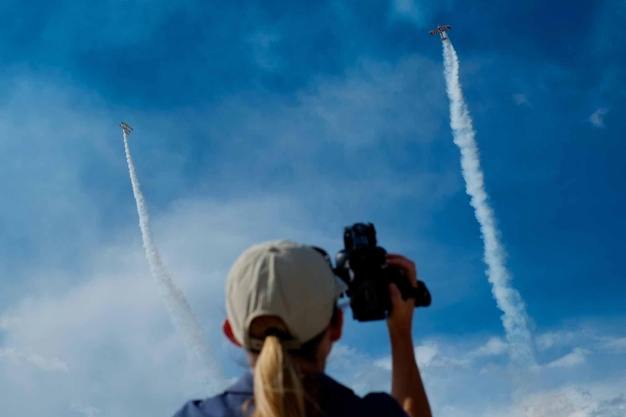 An onlooker videotapes stunt pilots flying during the Wheels and Wings airshow in Eagle, Colo. on Saturday, Sept. 26, 2014.