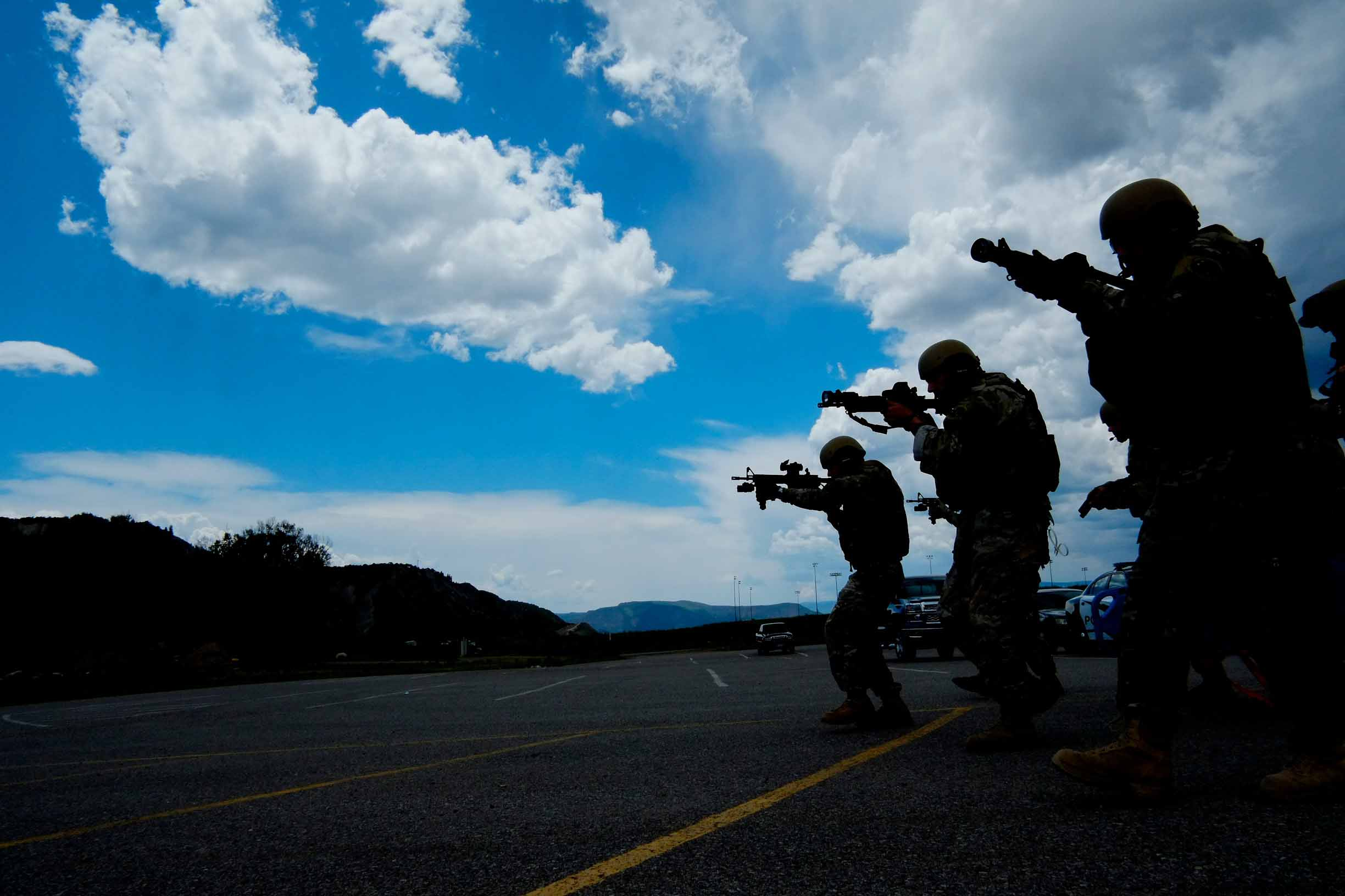 Members of Eagle County's Special Operations Unit, all local officers including two doctors, swiftly move across a parking lot to a staged victim during a training exercise in Eagle, Colo. on Thursday, June 12, 2014.