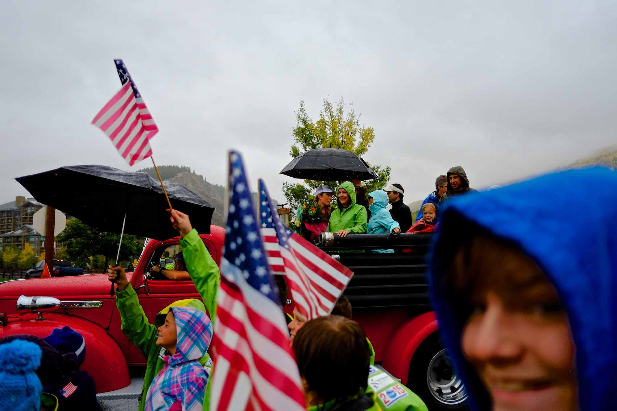 Children of Ski and Snowboard Club Vail raise flags and umbrellas as they march along Mikaela Way in Avon, Colo. on Monday, Sept. 29, 2014. Olympic gold medalist Mikaeala Shiffrin, in a white hat beneath an umbrella, followed in an antique firetruck.