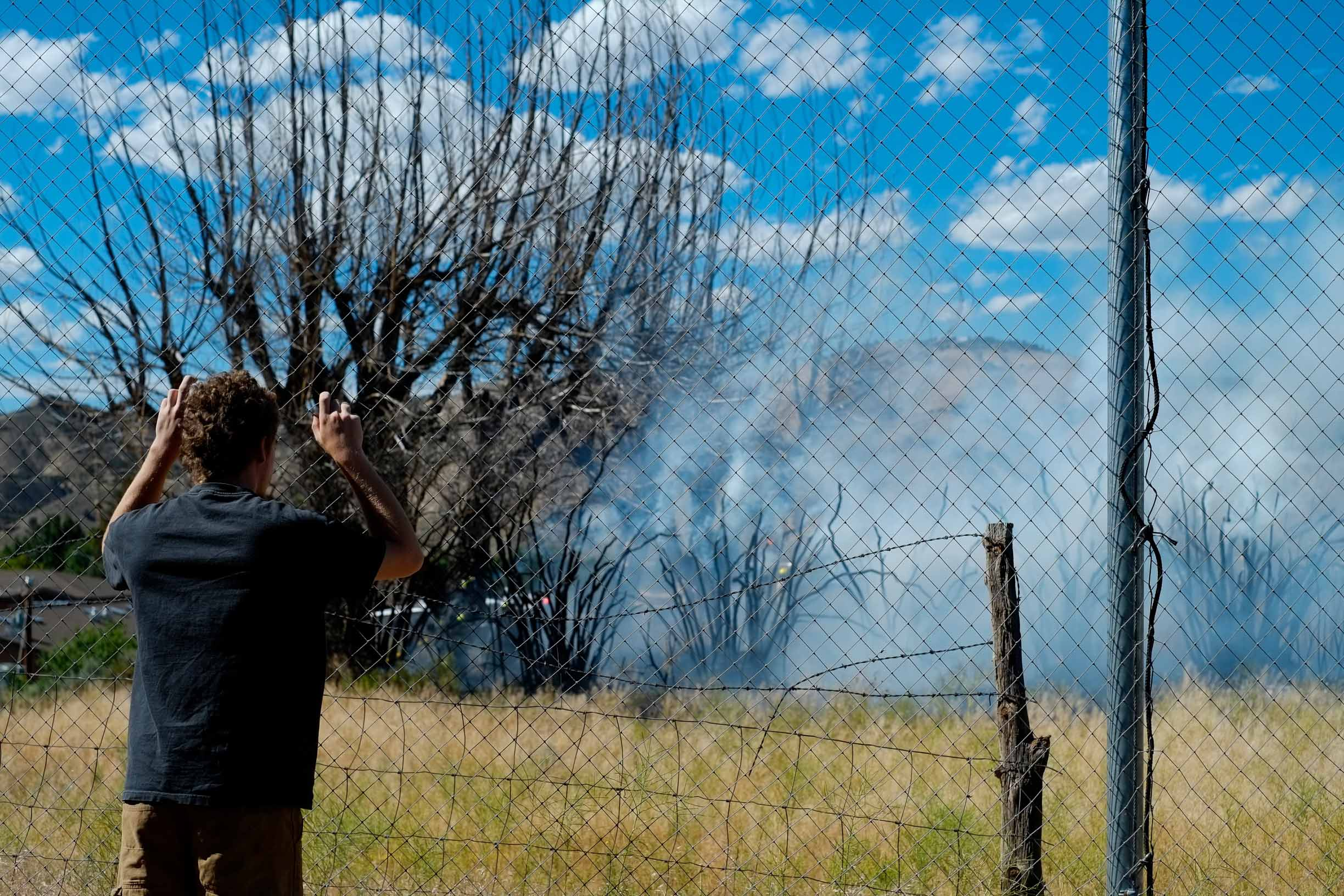 A bystander watches as smoke billows from charred trees after a fire in Gypsum, Colo. on Sunday June 29, 2014. The fire was at a risk of spreading due to high winds and the county's current drought.