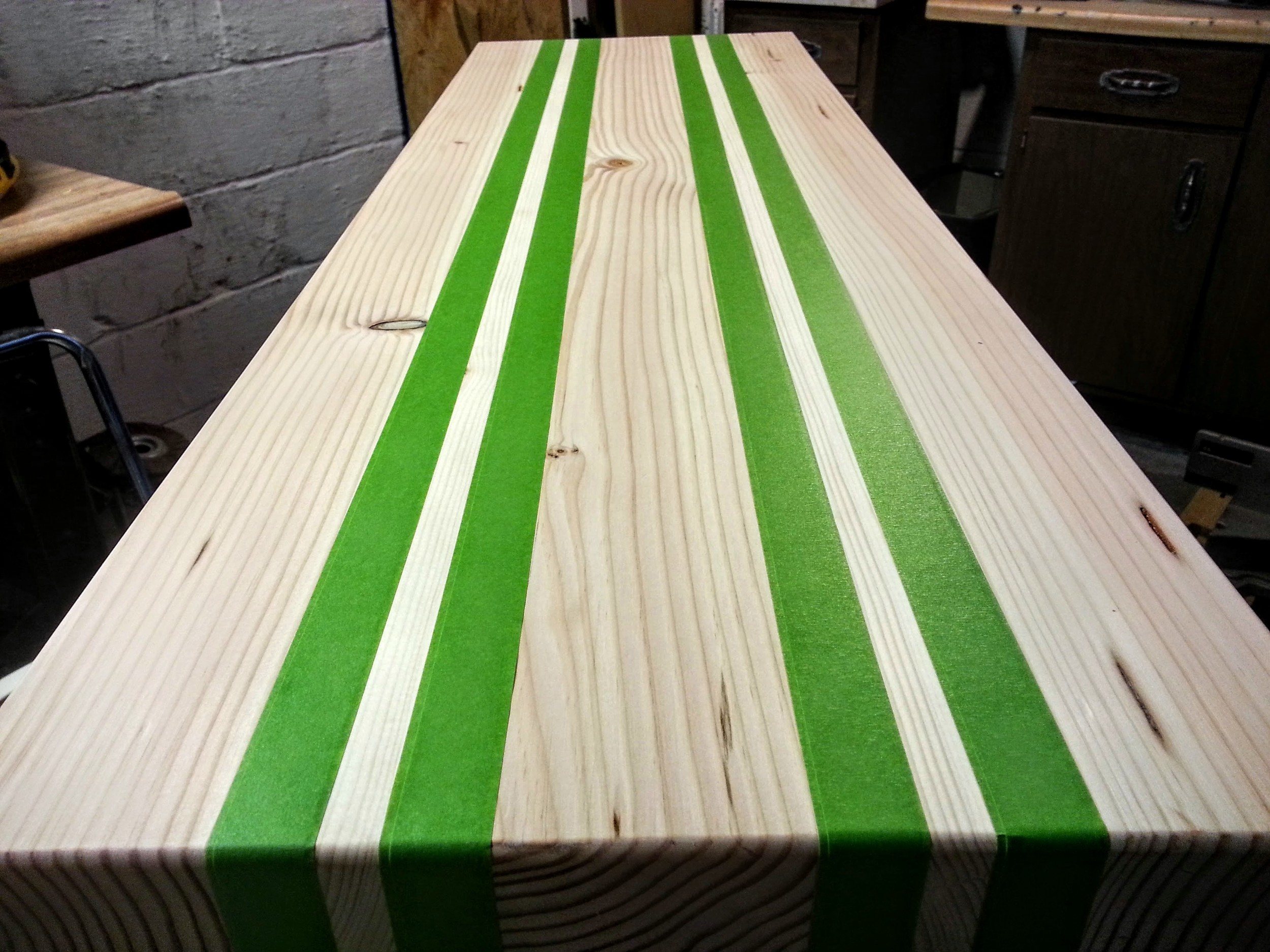 Masking off every other board with FrogTape to keep the stain from bleeding across boards