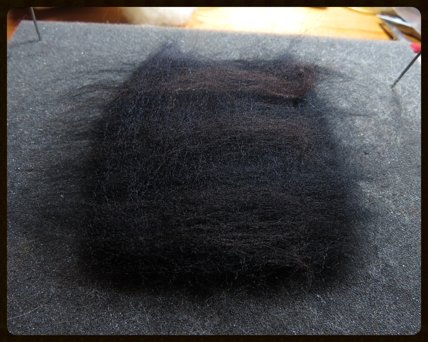 5. When I needlefelt black creatures, I like to add a little dark-colored woolto the black. It makes the finished black color a little less dull-looking. Here, I added some dark chocolate brown and a little navy blue.