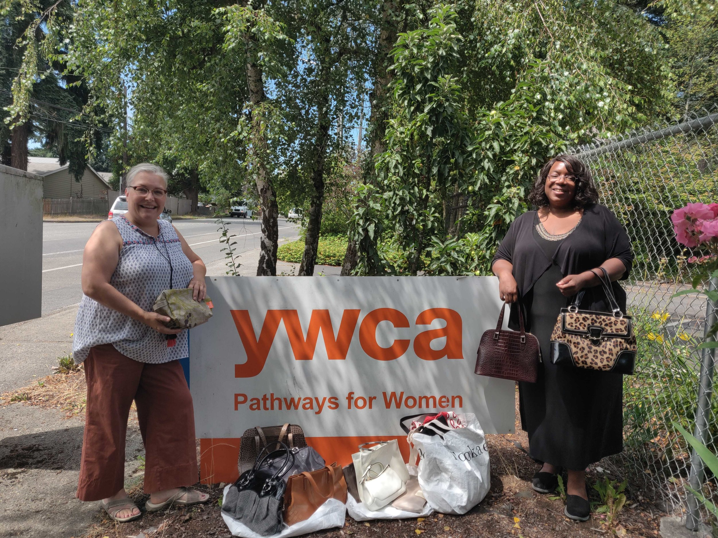 Erika Larimer, Koné Consulting and  Alicia Crank,  YWCA Corporate Relations Officer and  candidate for Edmonds City Council  meet at YWCA's temporary housing site to exchange donated bags. The site features 28 apartments, a small playground and garden and gives women and their children a safe haven while awaiting permanent housing.