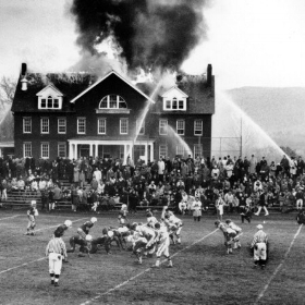 In Robert Van Fleet's well-known photograph, spectators in Massachusetts divided their attention as the Mount Hermon football team hosted Deerfield Academy while a fire burned in a Mount Hermon science building on Nov. 20, 1965. Credit Robert S. Van Fleet/Associated Press