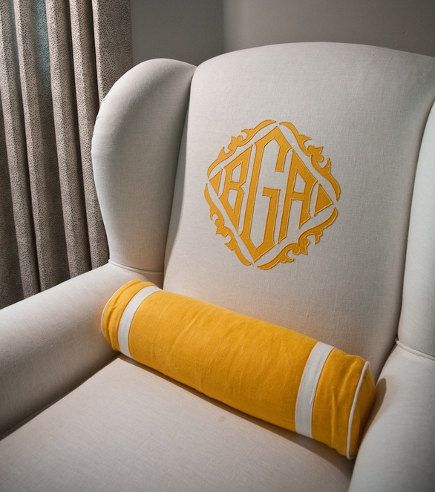 A wingback chair upholstered in linen with an embellished monogram and coordinating bolster