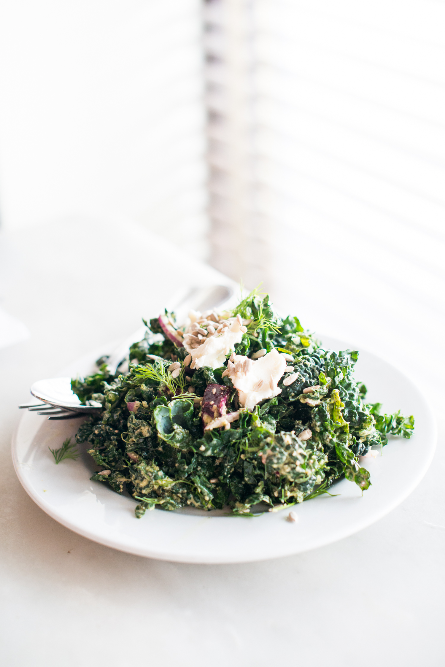 Kale salad with roasted beets, onion, goat cheese, and sunflower seed dressing.