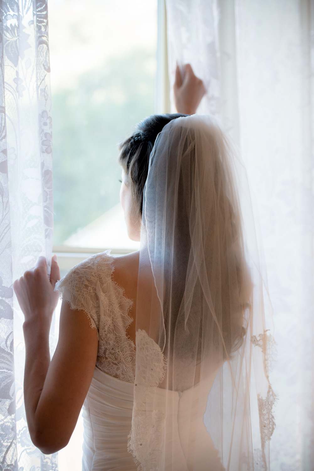 Bride at the window - It was a perfect opportunity when she was looking for someone outside, so you think. Nah we just asked her to pose:)