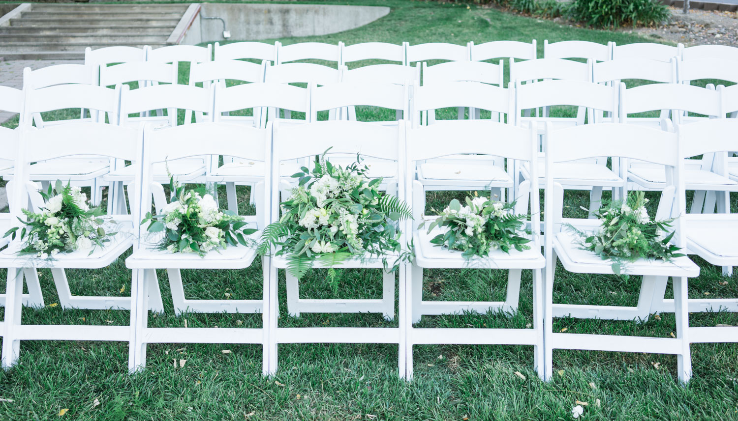 White chairs and green bouquets being set up for the wedding ceremony.