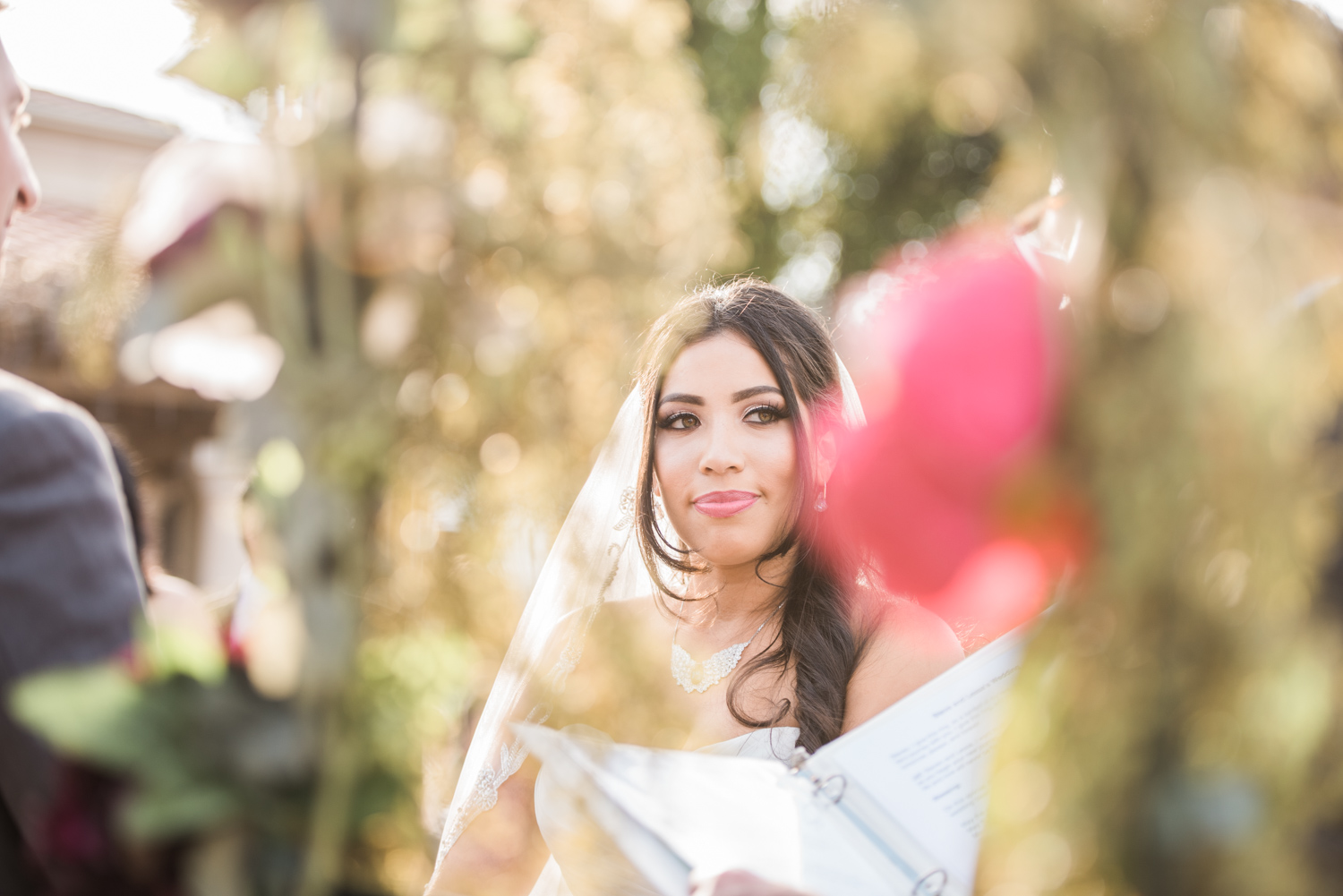 Bride at the alter | Picture shot through the flowers