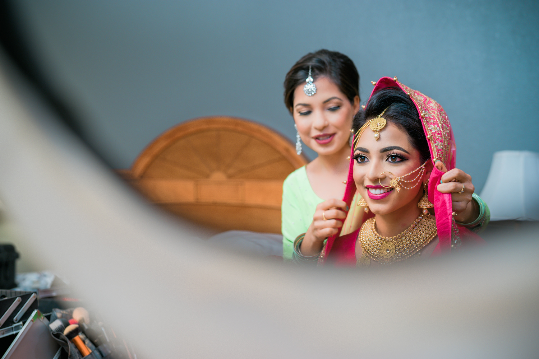 Bridesmaid helping the punjabi bride with the veil.