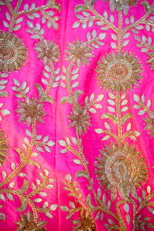 Fuchsia pink bridal lehenga with golden embroidery.